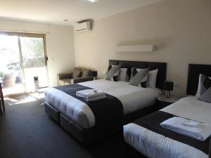 A bed or beds in a room at Wine Village Motor Inn