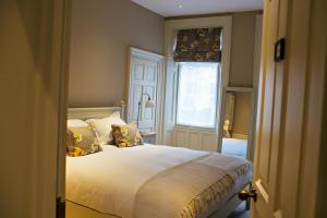 A bed or beds in a room at Houndgate Townhouse