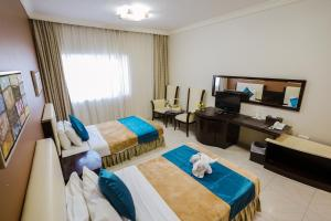 A bed or beds in a room at Crystal Plaza Hotel
