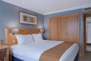 A bed or beds in a room at Holiday Inn London Kensington Forum, an IHG Hotel