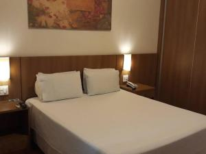 A bed or beds in a room at Premier Parc Hotel