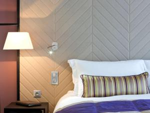 A bed or beds in a room at Sofitel Strasbourg Grande Ile