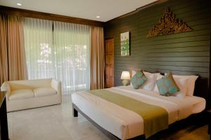 A bed or beds in a room at Royal River Kwai Resort and Spa