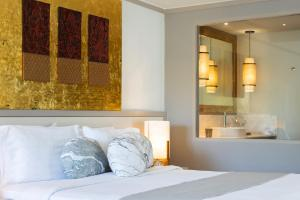 A bed or beds in a room at Rocky's Boutique Resort - SHA Plus