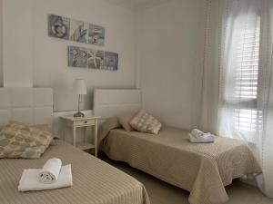 Cama o camas de una habitación en Billy's Beachfront Apartment with pool access