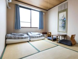 A bed or beds in a room at Stay Inn KOTO