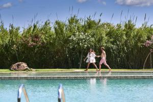 The swimming pool at or near Baia Di Chia Resort Sardinia, Curio Collection By Hilton