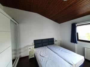 A bed or beds in a room at Ferienhaus Stausee Eifel