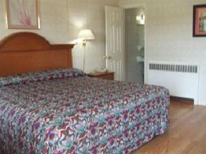 A bed or beds in a room at Robin Hood Motel