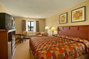 A bed or beds in a room at Baymont by Wyndham Tuscola