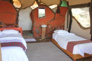 Un ou plusieurs lits dans un hébergement de l'établissement Lion's Cave Camp, Samburu
