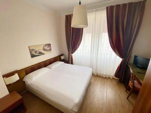A bed or beds in a room at Grand Hotel Regina Salsomaggiore