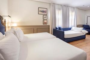 A bed or beds in a room at H10 Corregidor Boutique Hotel