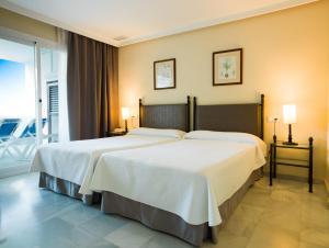 Een bed of bedden in een kamer bij Aparthotel Monarque Sultán