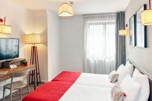 A bed or beds in a room at Appart'City Strasbourg Centre