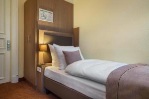 Ein Bett oder Betten in einem Zimmer der Unterkunft Novum Hotel Alster Hamburg St. Georg