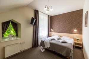 A bed or beds in a room at Hotel Sigulda