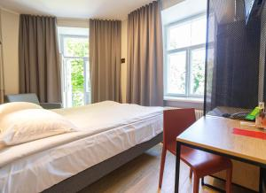 A bed or beds in a room at Rija Old Town Hotel
