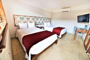 A bed or beds in a room at Hotel Caribe Merida Yucatan