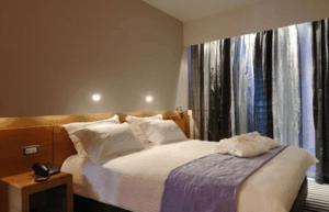 A bed or beds in a room at Galaxy City Center Hotel