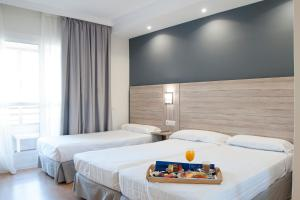 A bed or beds in a room at Hotel Maya Alicante