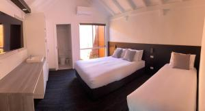 A bed or beds in a room at Railway Motel Myrtleford
