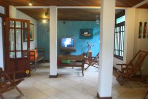 A television and/or entertainment centre at Pousada Paraíso Ilha Grande
