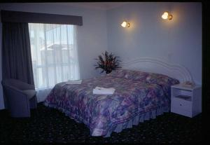 A bed or beds in a room at Runaway Bay Motor Inn