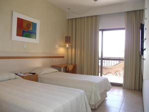 A bed or beds in a room at Catussaba Business Hotel