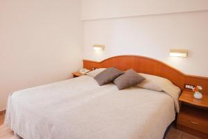 A bed or beds in a room at Hotel Odisej
