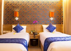 A bed or beds in a room at Natya Hotel Kuta