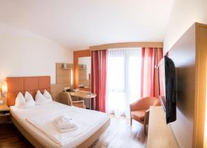 A bed or beds in a room at Quellenhotel Heiltherme Bad Waltersdorf - 2-Thermenresort