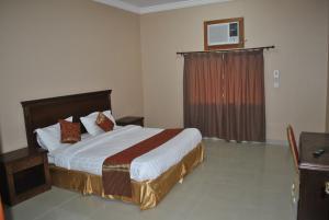 سرير أو أسرّة في غرفة في منازل الستين للشقق المفروشة