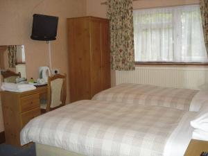 A bed or beds in a room at Bridge Guest House