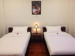 A bed or beds in a room at Thanlwin Guesthouse