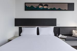 A bed or beds in a room at ibis Adelaide