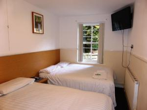 A bed or beds in a room at Old Vicarage Hotel
