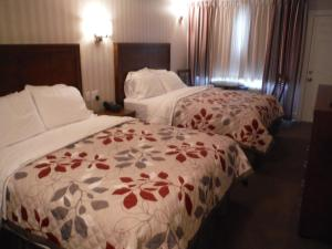 A bed or beds in a room at Motel Beausejour