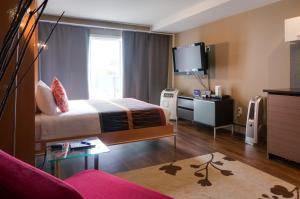 A bed or beds in a room at NUVO Hotel Suites for Residence
