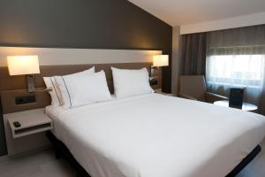A bed or beds in a room at AC Hotel by Marriott Colón Valencia