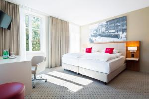 A bed or beds in a room at Hotel Wartmann am Bahnhof