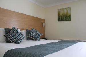 A bed or beds in a room at Old Rectory Hotel, Crostwick