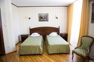 A bed or beds in a room at Pensiunea Eden Caransebes