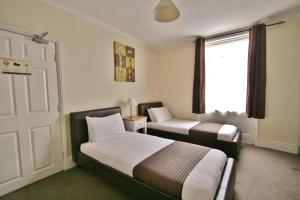 A bed or beds in a room at Central Hotel Cheltenham by Roomsbooked