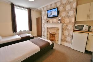 A television and/or entertainment centre at Central Hotel Cheltenham by Roomsbooked