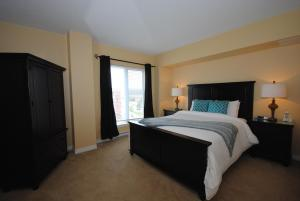 A bed or beds in a room at Premiere Suites - Moncton, Assomption Boulevard