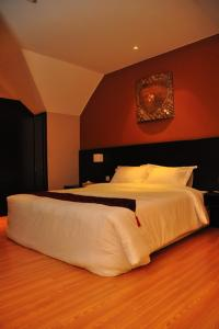 A bed or beds in a room at Tat Place Hotel