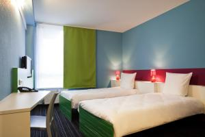 A bed or beds in a room at ibis Styles Duesseldorf-Neuss