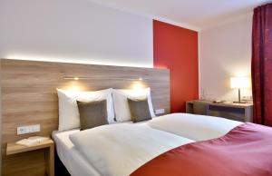 A bed or beds in a room at das seidl - Hotel & Tagung - München West