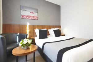 A bed or beds in a room at Kyriad Marseille Centre Paradis-Préfecture